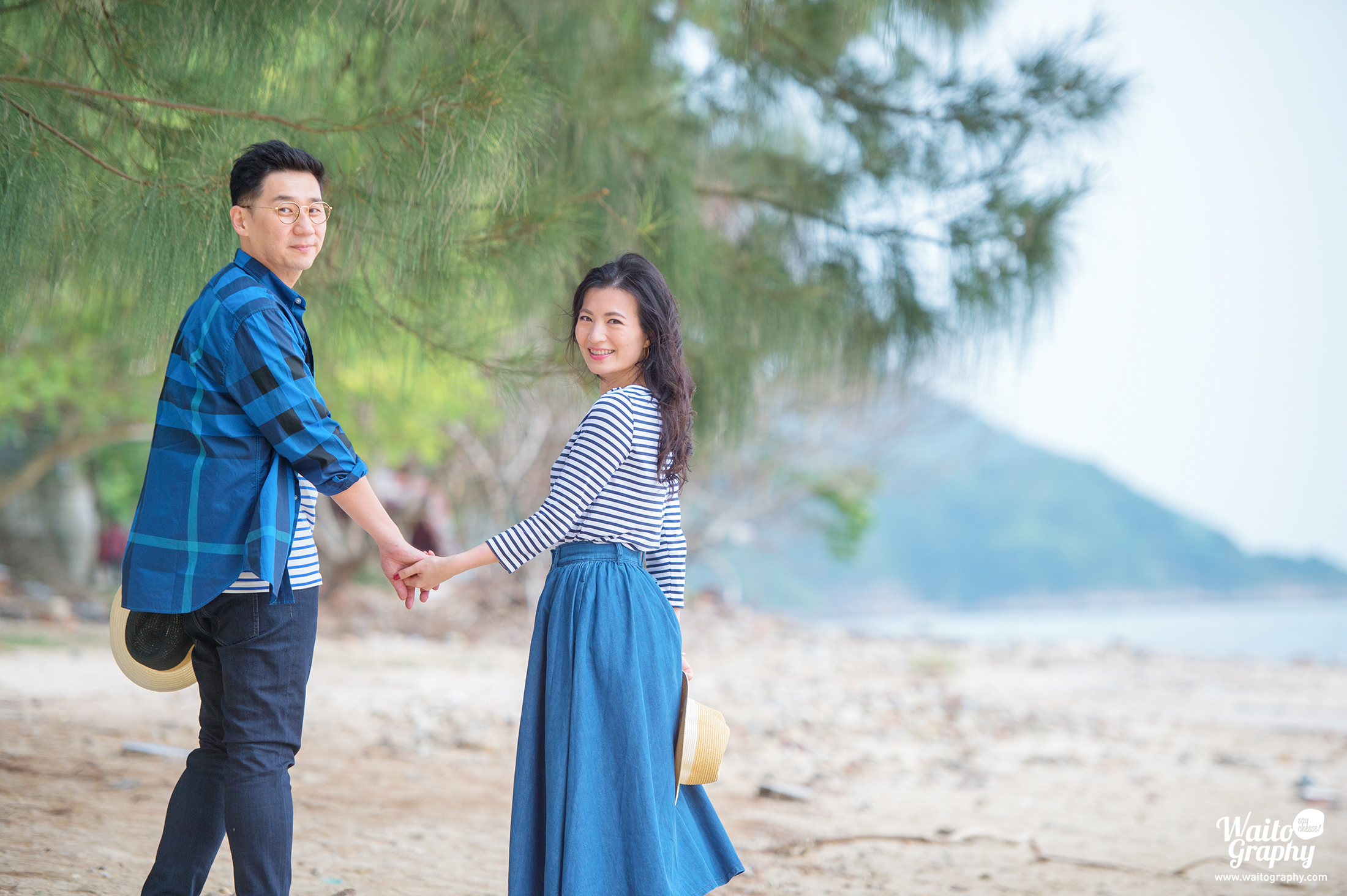 Hong Kong engaged couple walking hand in hand taking pre wedding photo at the beach